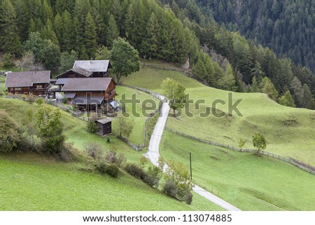 Alp farm on the slope with fields - stock photo