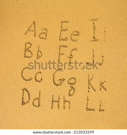 Alphabet (A-L) written on a sand beach.  - stock photo