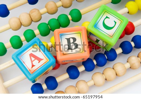 Alphabet blocks and abacus isolated on white - stock photo