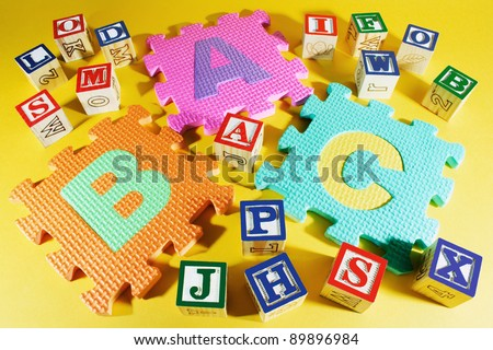 Alphabet Blocks and Alphabet Puzzles on Yellow Background - stock photo