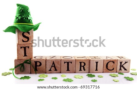 """Alphabet blocks arranged to spell """"St. Patrick,"""" adorned with sparkly shamrocks and a green hat.  Isolated on white with space for your text. - stock photo"""