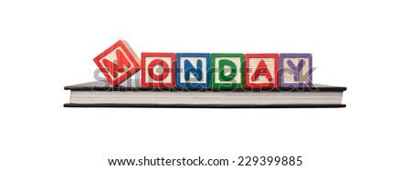 Alphabet blocks forming the word MONDAY on a book isolated on white background  - stock photo