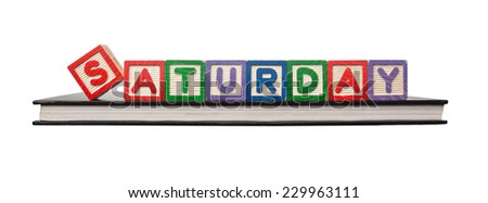Alphabet blocks forming the word SATURDAY on a book isolated on white background - stock photo