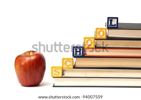 Alphabet blocks spell out the word school on a pile of books. - stock photo
