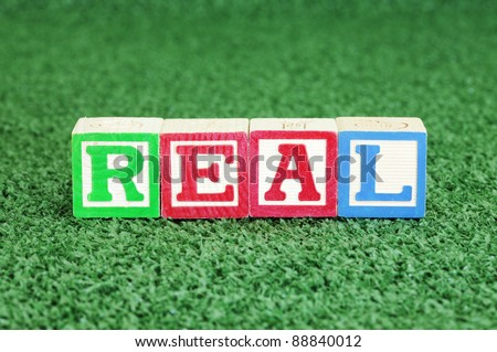 Alphabet Blocks Spelling out Real on Artificial Grass - stock photo