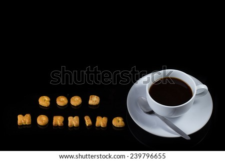 Alphabet cracker with cup of coffee on black background (spelling GOOD MORNING) - stock photo