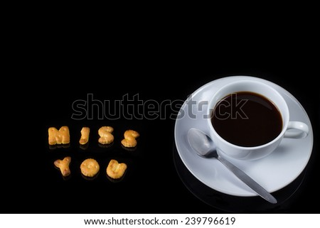 Alphabet cracker with cup of coffee (spelling MISS YOU) - stock photo