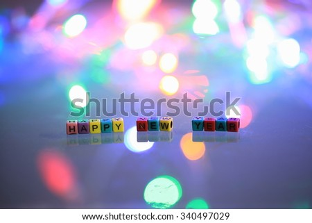 Alphabet Happy New Year with refelction and colorful  bokeh background
