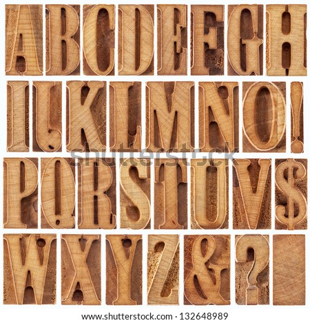 alphabet in modern letterpress wood type printing blocks (unused), a collage of 26 isolated letters, question mark, exclamation point, ampersand and dollar sign - stock photo