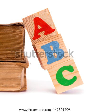 Alphabet letter ABC blocks for kids on old books isolated on white - stock photo