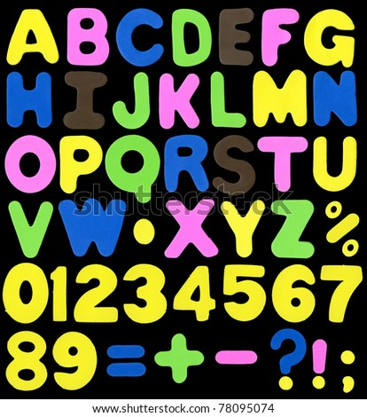 Alphabet made of neon color sponge alike soft plastic, containing letters, numbers, signs and symbols isolated on black background - stock photo