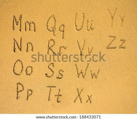 Alphabet (2 part of 2) written on a sand beach. - stock photo
