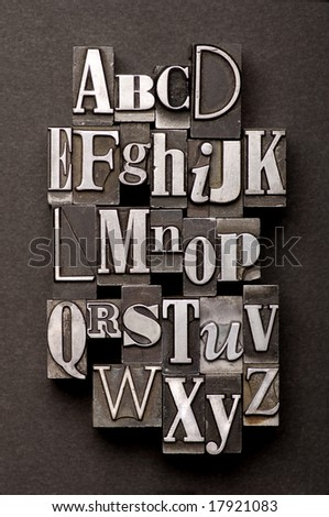 Alphabet photographed using a mix of vintage letterpress characters on a black textured background. - stock photo