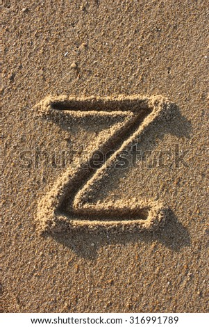 Alphabet's letter Z handwritten in sand on the beach, at sunrise. - stock photo