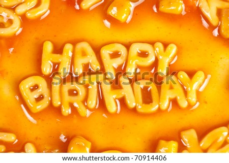 Alphabet shaped pasta forming HAPPY BIRTHDAY in tomato sauce - stock photo