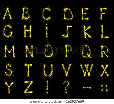 Alphabet sparklers on black background - stock photo