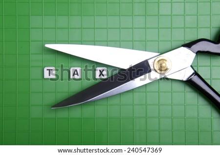 Alphabet TAX with scissor on the green box platform  - stock photo