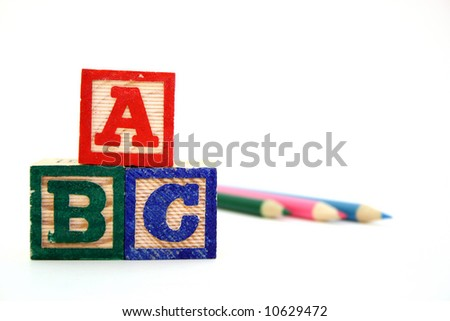 alphabet wood blocks and colored pencils over a white surface