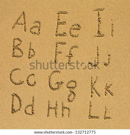 Alphabet written on a sand beach. (A-L) - stock photo