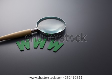 Alphabet WWW and magnifier glass on the gray background