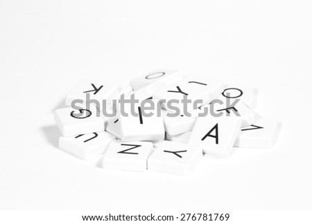 Alphabets in a pile. Image in black and white.