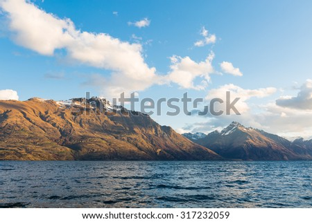 alpine and lake landscape with snow on top of the mountain - stock photo