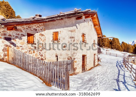 Alpine chalet surrounded by a fence in the snow among snowy peaks and pine forest on a bright sunny day in winter - stock photo