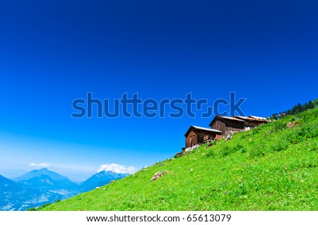 Alpine chalets on green mountain slope under blue sky. French Apls. - stock photo