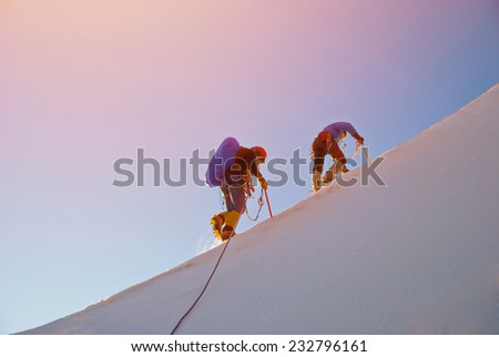 Alpine climbers balances on the ice snowfield - stock photo