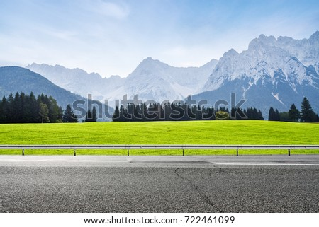 Alpine green meadow and asphalt road.  Mountains on background. Landscape in sunny summer day
