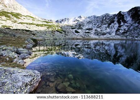 Alpine lake reflection - Retezat Mountains, Southern Carpathians, Romania - stock photo