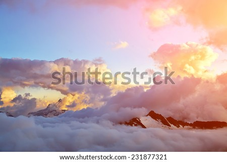 alpine landscape with peaks covered by snow and clouds. natural mountain background - stock photo