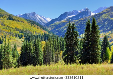 alpine landscape with snow covered mountains in Colorado during foliage season - stock photo