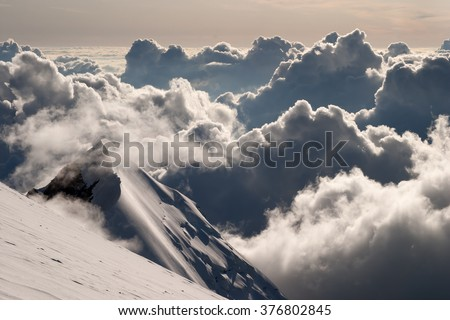 Alpine landscape with steep slopes and dramatic cloudy sky. - stock photo