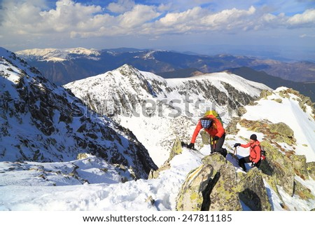 Alpine landscape with winter climbers ascending a snow covered ridge in sunny day - stock photo