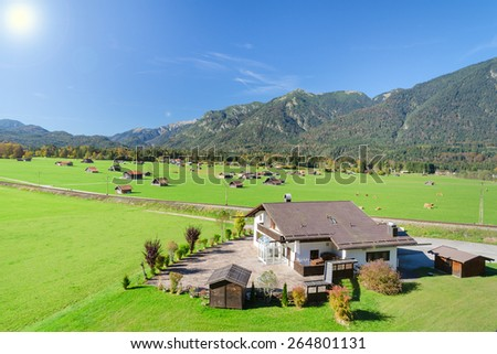 Alpine mountains summer landscape with green meadow and pasture in valley and blue sky - stock photo