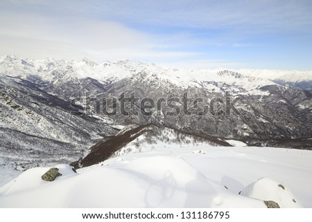 Alpine mountainscape in winter with snowy slope, valleys and clouds