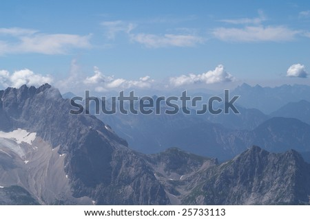 Alpine mountins landscape with haze and clouds - stock photo