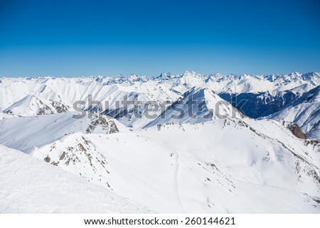 Alpine panorama showing snow covered mountains - stock photo