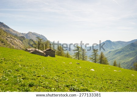 Alpine pasture and shepherd's huts set in amazing mountain scenery in spring season. Lush green meadows in the foreground. Piedmont, italian Alps. - stock photo