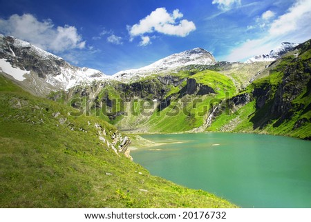 Alpine peaks covered by snow and a beautiful crystal clear lake