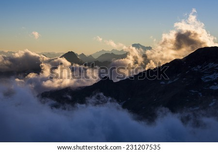 Alpine peaks in the clouds seen from Mantova hut on Monte Rosa, Valle Aosta, Italy