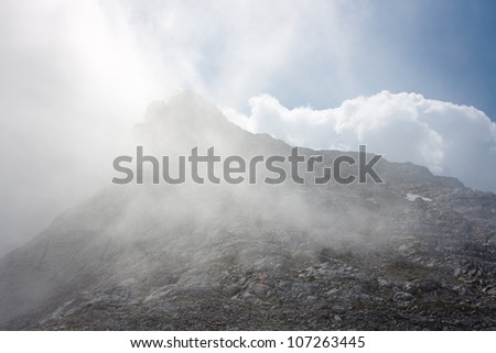 Alpine scenery: mountain peak in the clouds