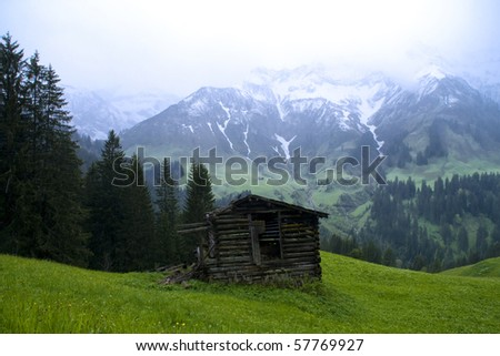 Alpine scenery with barn shed and snow mountain background