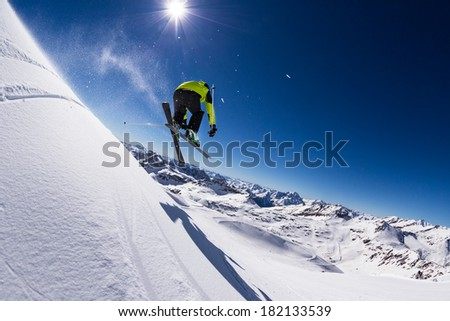 Alpine skier in high jump, blue sky on background