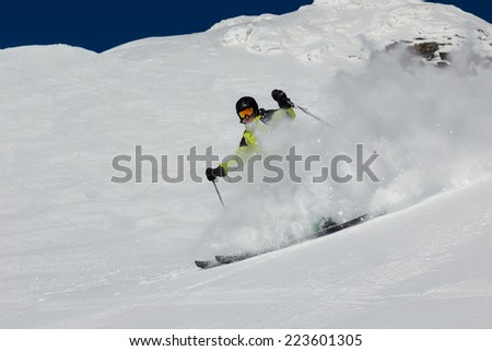 Alpine skier skiing downhill, blue sky on background - stock photo