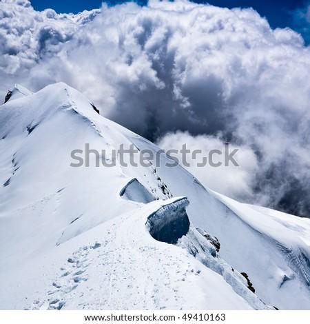 Alpine snow ridge with dramatic sky - stock photo