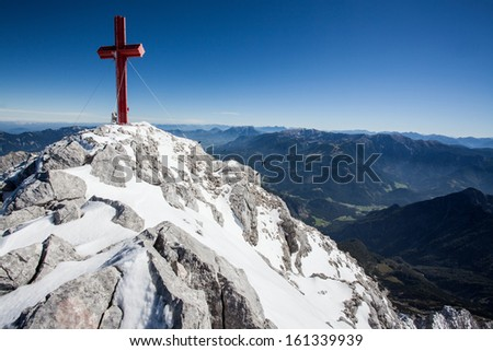 Alpine summit in the Austrain Alps with huge summit cross. - stock photo