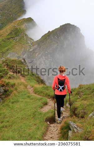 Alpine trail and woman hiker walking above the clouds