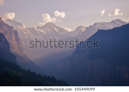 Alpine valley at Sunset- Sun sets over an alpine valley, Switzerland - stock photo